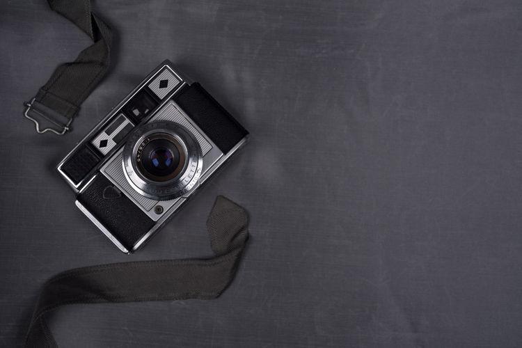 Directly above shot of vintage camera on black background