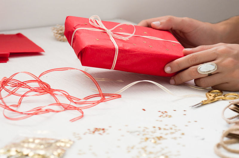 Cropped image of hand holding gift box on table