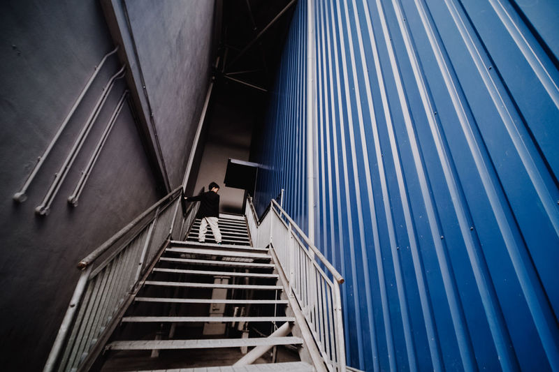 Low angle view of boy standing on staircase in building