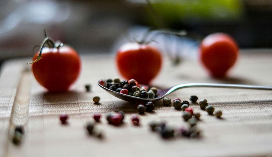 Peppercorns and cherry tomatoes on wooden table