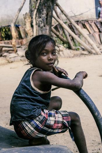 Full length of girl sitting outdoors