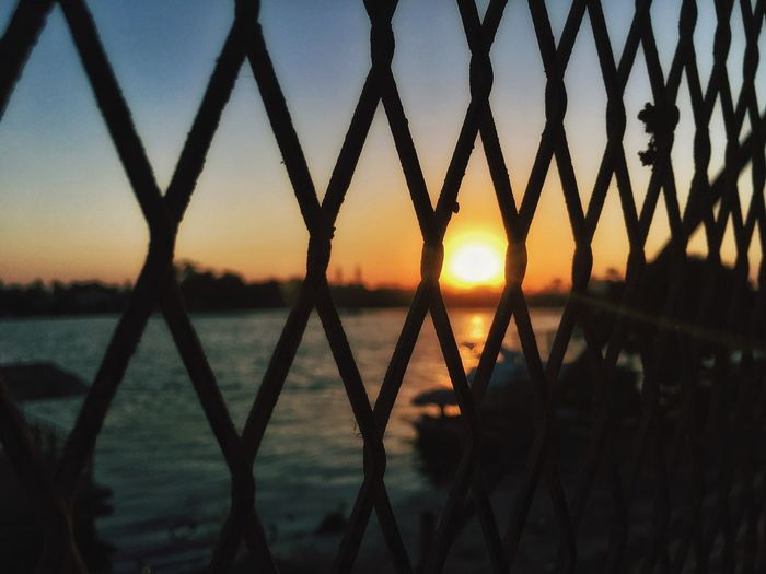 🏞 Sunset Water Sky Fence Silhouette Barrier Nature Protection Safety Security Metal No People Boundary Orange Color Scenics - Nature Chainlink Fence Lake Beauty In Nature Tranquility Sun