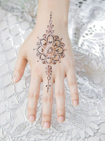 Close-up of woman hand with tattoo on bed