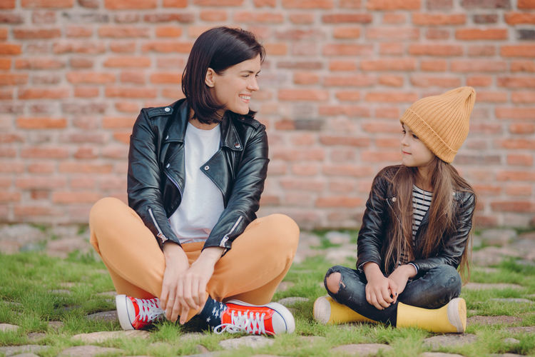 Smiling mother talking with daughter while sitting on land against brick wall