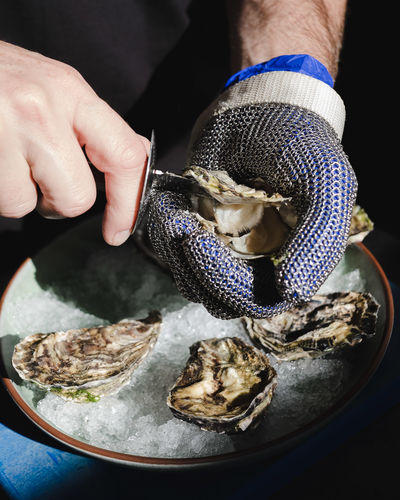 Human Hand Hand One Person Human Body Part Food Food And Drink Real People Holding Freshness Indoors  Preparation  Unrecognizable Person Close-up Focus On Foreground Body Part Seafood Occupation High Angle View Finger Preparing Food Oyster