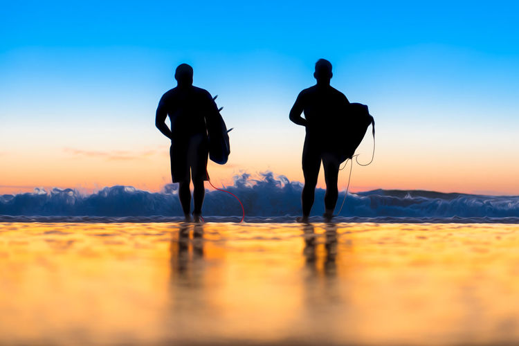 Rear view of men carrying equipment while walking towards sea against sky during sunset
