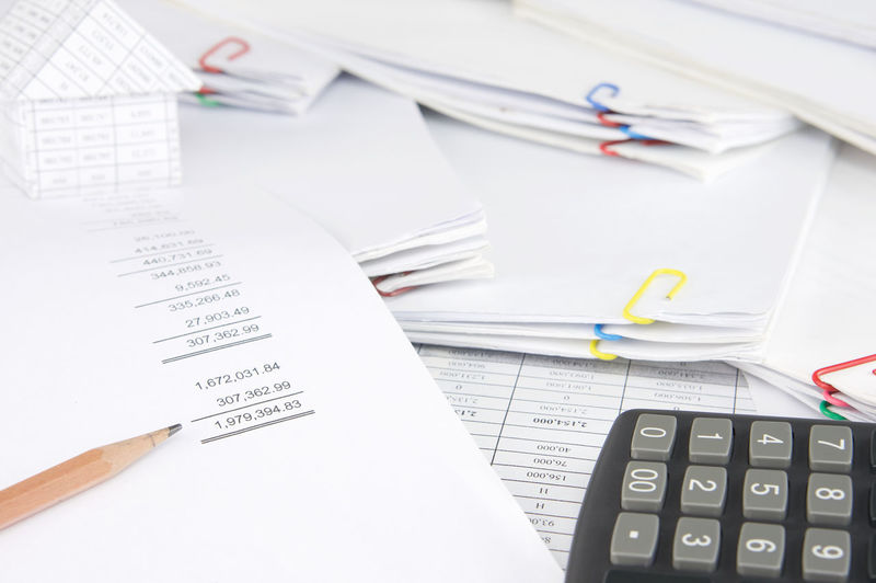 High angle view of calculator and pencil with model house on financial documents