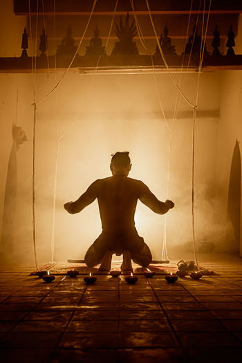 Full length of silhouette man standing at illuminated stage