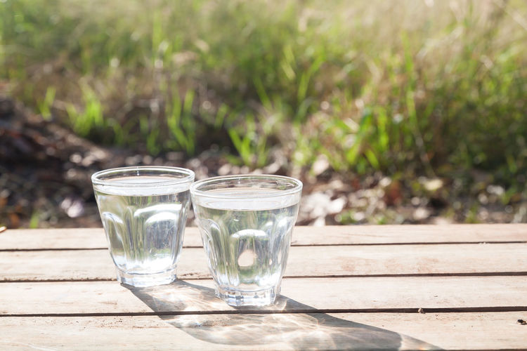 Glasses of water on wooden table with nature in background, Healthy lifestyle Wood - Material Water Table Sunlight Refreshment Outdoors No People Nature Healthy Freshness Food And Drink Focus On Foreground Drinking Glass Drink Day Thirsty  Pure Lifestyle Kanchanaburi