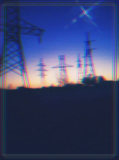Silhouette of electricity pylon against sky at sunset
