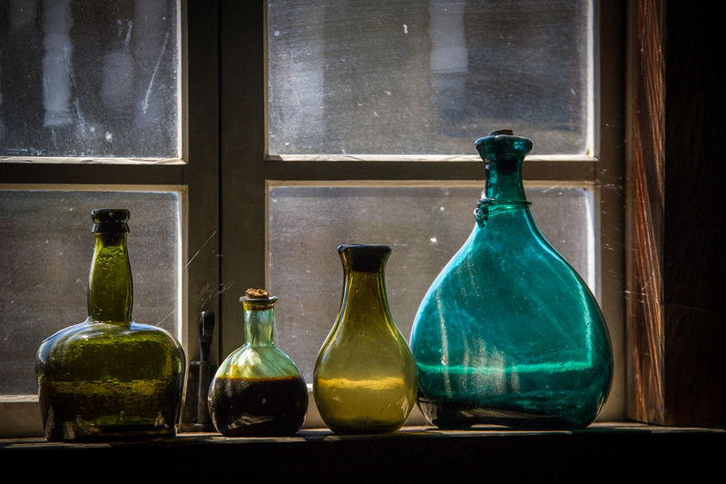 Close-up of glass bottles on window sill