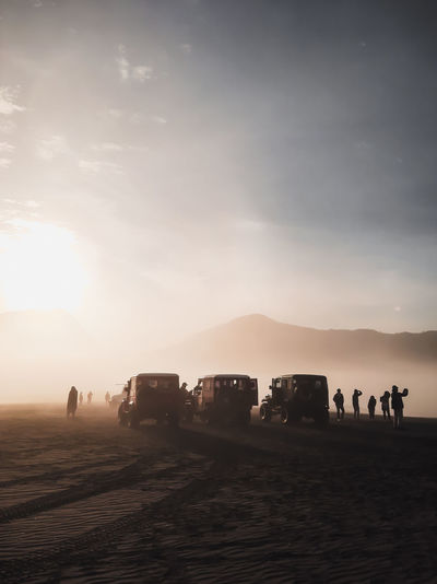 Vehicles and people standing in desert