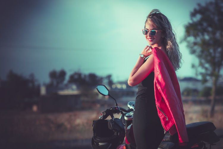Portrait of smiling woman wearing sunglasses standing by motorcycle