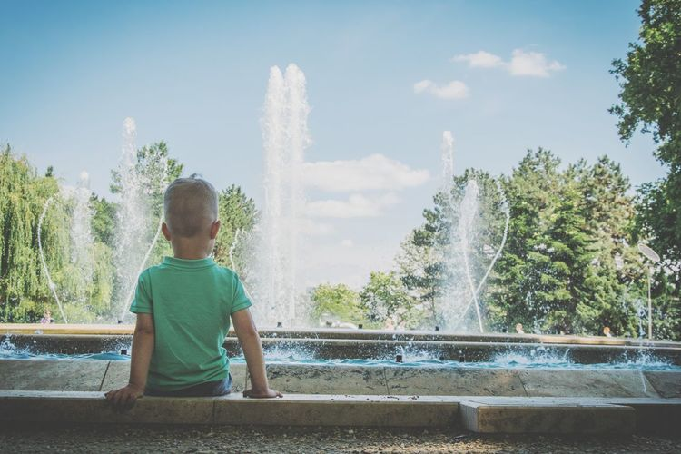 Rear view of boy sitting by fountain