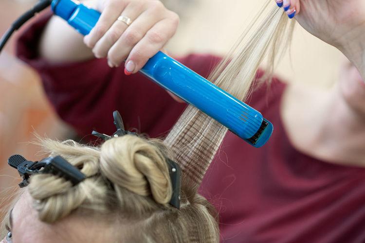 Close-up of hair dresser shaping customer hair at salon