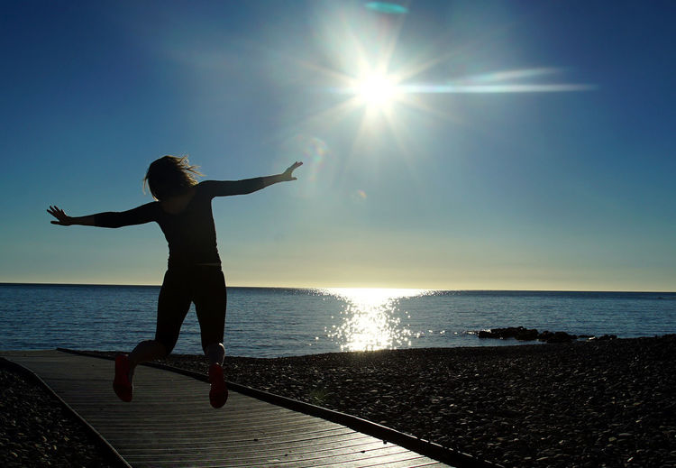 Rear view of woman jumping over boardwalk by sea against sky during sunny day