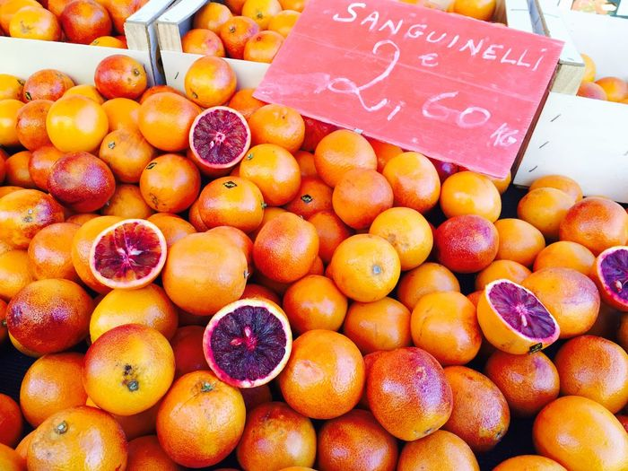 High Angle View Of Fresh Blood Oranges Heap With Price Tag At Market Stall