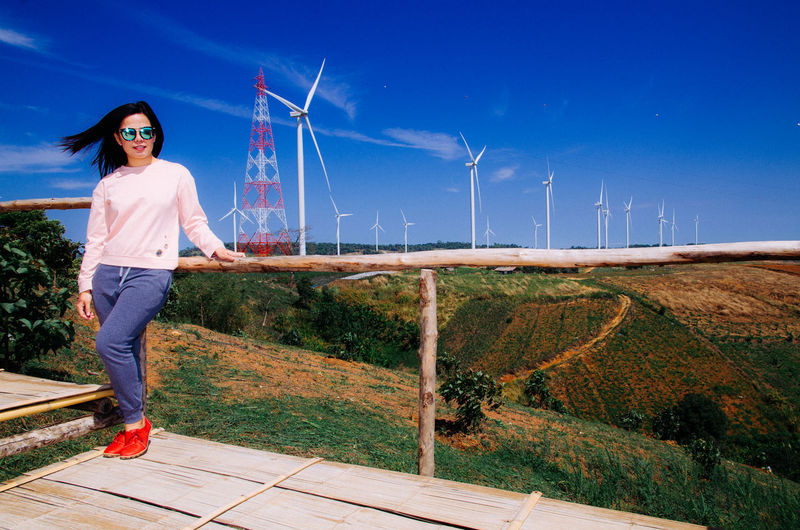 Full length portrait of young woman standing against wind turbines