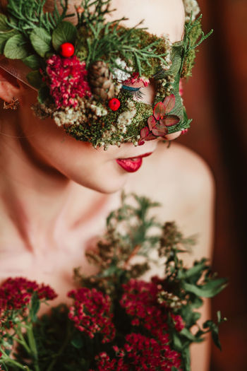 Close-up of woman with flower mask looking away