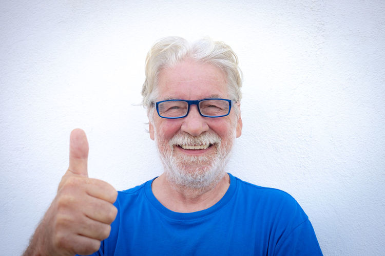 Portrait of smiling senior man gesturing against wall