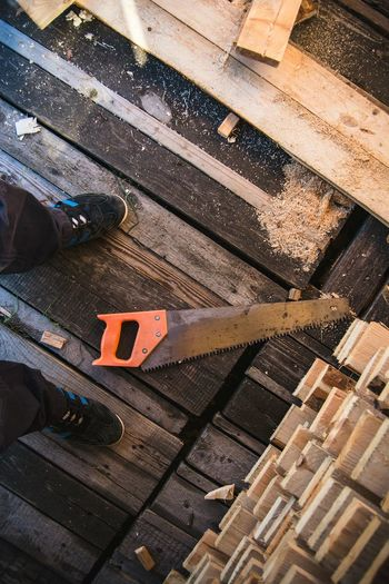 Low angle view of man standing by hand saw by planks on floorboard