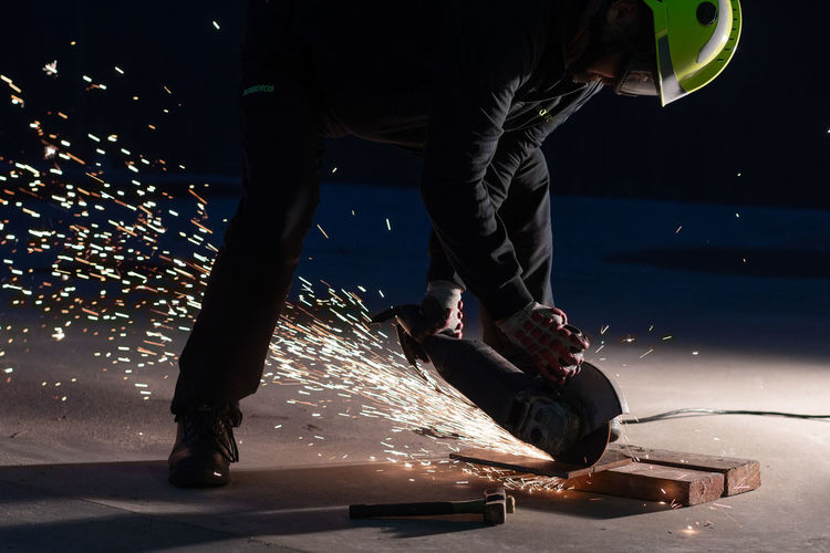 Low section of man skateboarding at night
