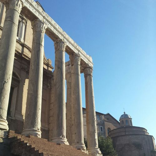 Low angle view of roman forum against blue sky
