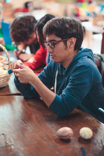 Young man decorating easter eggs while sitting on table indoors