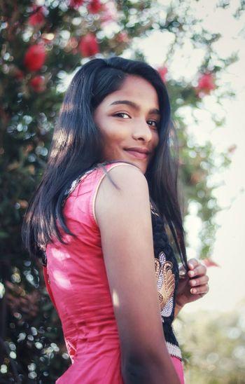 Portrait of smiling teenage girl standing against plants
