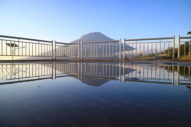 Reflection of bridge in lake against clear blue sky