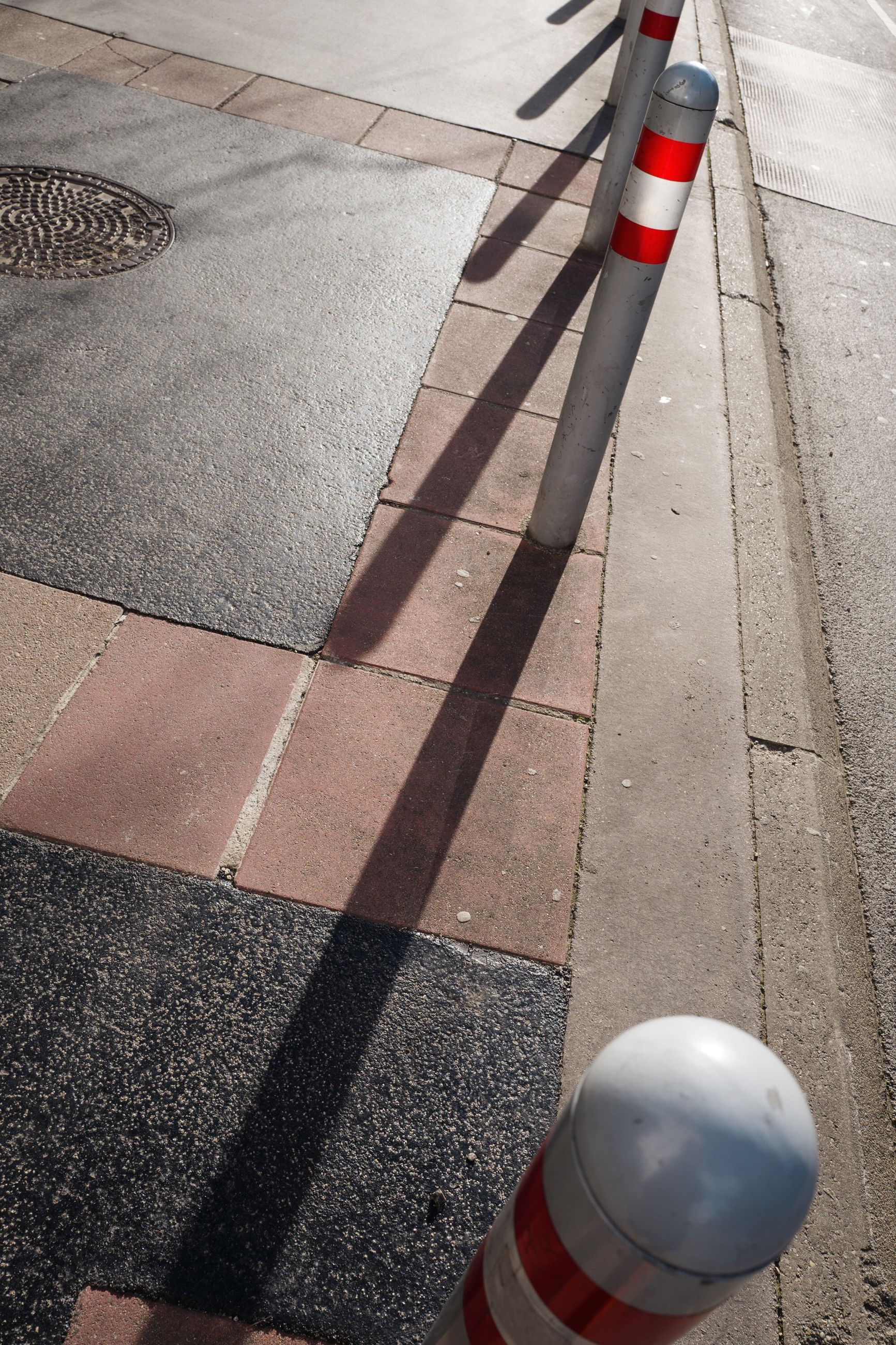 high angle view, transportation, road, sign, symbol, city, street, day, safety, road marking, marking, traffic cone, cone, striped, security, protection, guidance, shadow, outdoors, one person, dividing line
