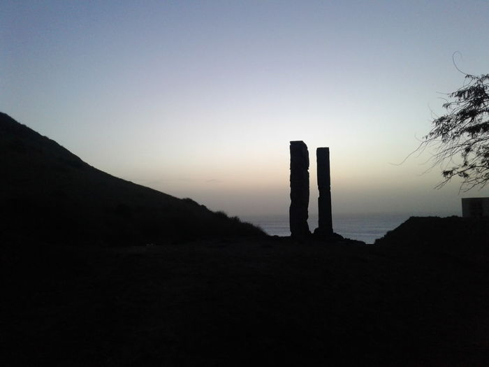 Silhouette wooden posts on mountain against sky during sunset