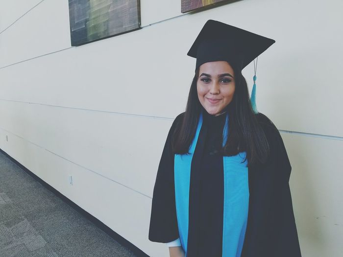 Portrait Of Young Woman Wearing Graduation Gown While Standing By Building