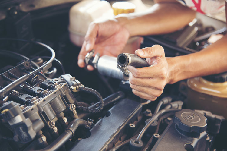 Cropped image of mechanic working on car engine