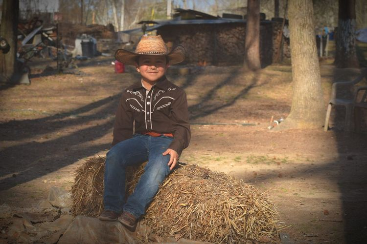 Portrait Of Smiling Boy Wearing Cowboy Hat Sitting On Hay Over Field