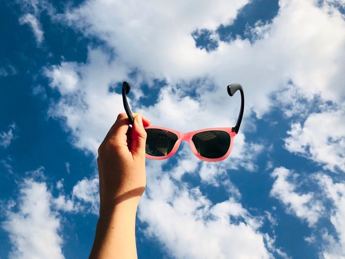 Hand holding pink sunglasses against summer blue sky covered with fluffy white clouds Cloud - Sky Sky Human Hand Hand Human Body Part Low Angle View Nature Day One Person Body Part Holding Real People Lifestyles Human Finger Personal Perspective Finger Positive Emotion Love Outdoors