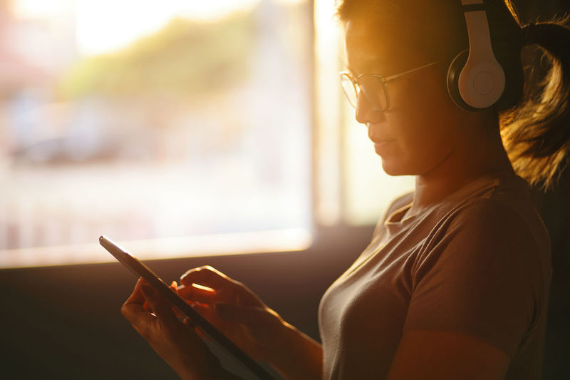 A woman uses a tablet during listening to music with the headphone