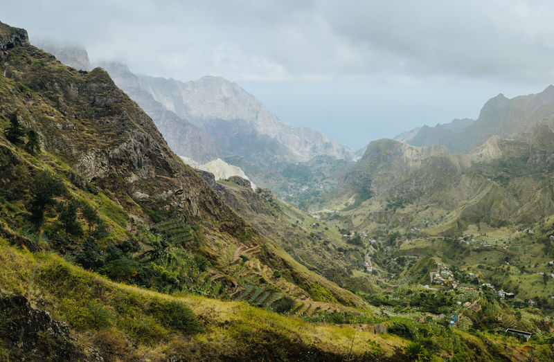 Gorgeous panorama view of a fertile Paul valley. Agriculture terraces in vertical valley sides, rugged peaks and motion clouds on horizon. Atlantic Ocean Cape Verde Endless Hiking Quaint  Rocky Coastline Trekking Canyon Cascade Clouds Destination Landscape_photography Mountain Range Paul Valley Plantation Ravine Remote Santo Antao Scenics Steep Sugarcane Tropical Climate Vegetation Viewpoint Volcanic Landscape