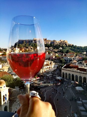 Toast to Dyonisus. Acropolis, Athens Backround Picture Glass Of Wine Rosé Skyscraper Sky Exlporing God Of Wine Dionysus Travel Destinations Journeys Discover Your City History Greek Mythology Human Hand Alcohol Drinking Glass Champagne Red Wine Champagne Flute Cocktail Rose Wine Urban Scene