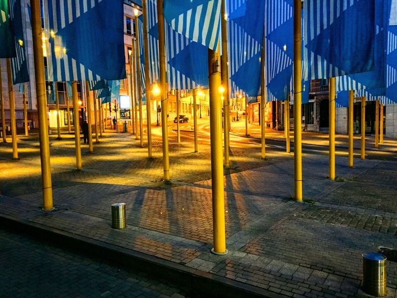 Place in Brussels filled with flags and yellow flagpoles Architecture Blue Building Exterior Built Structure City Illuminated Night No People Outdoors Sky Transportation