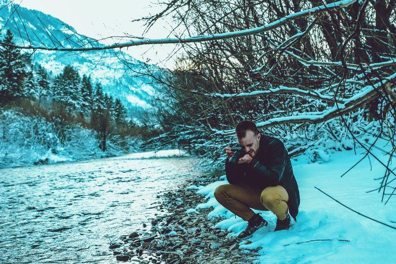 Man photographing through camera at lake during winter