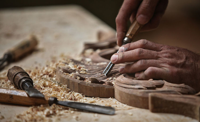 Cropped hands carving on wood in workshop