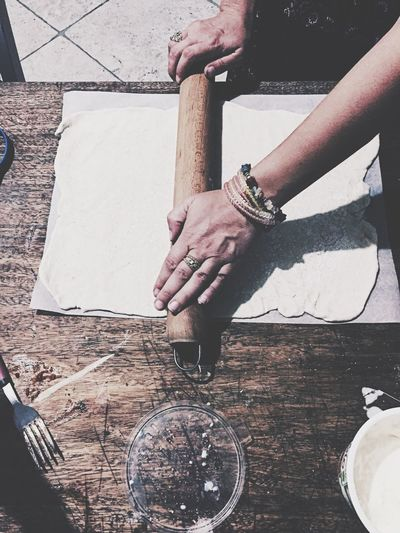 Cropped hands of woman rolling dough at table