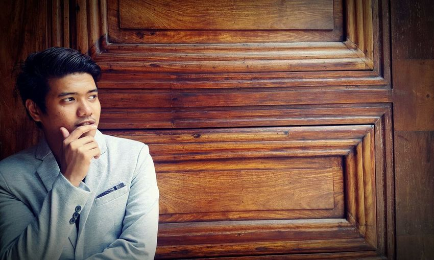 Thoughtful man looking away against wooden wall