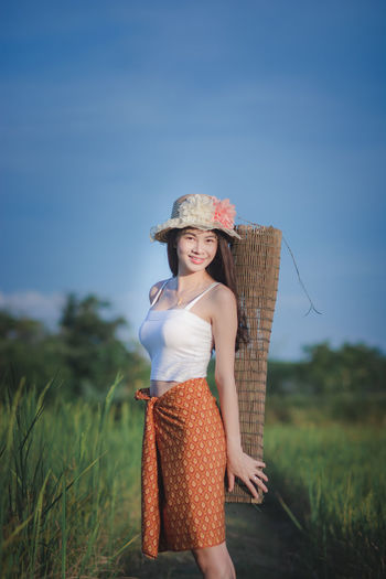 Smiling Field One Person Looking At Camera Land Women Happiness Standing Portrait Sky Hat Plant Clothing Nature Leisure Activity Adult Real People Three Quarter Length Beautiful Woman Fashion Sun Hat Outdoors