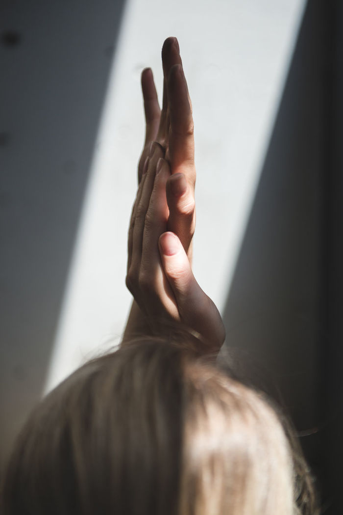 MIDSECTION OF WOMAN HAND WITH SHADOW ON WALL