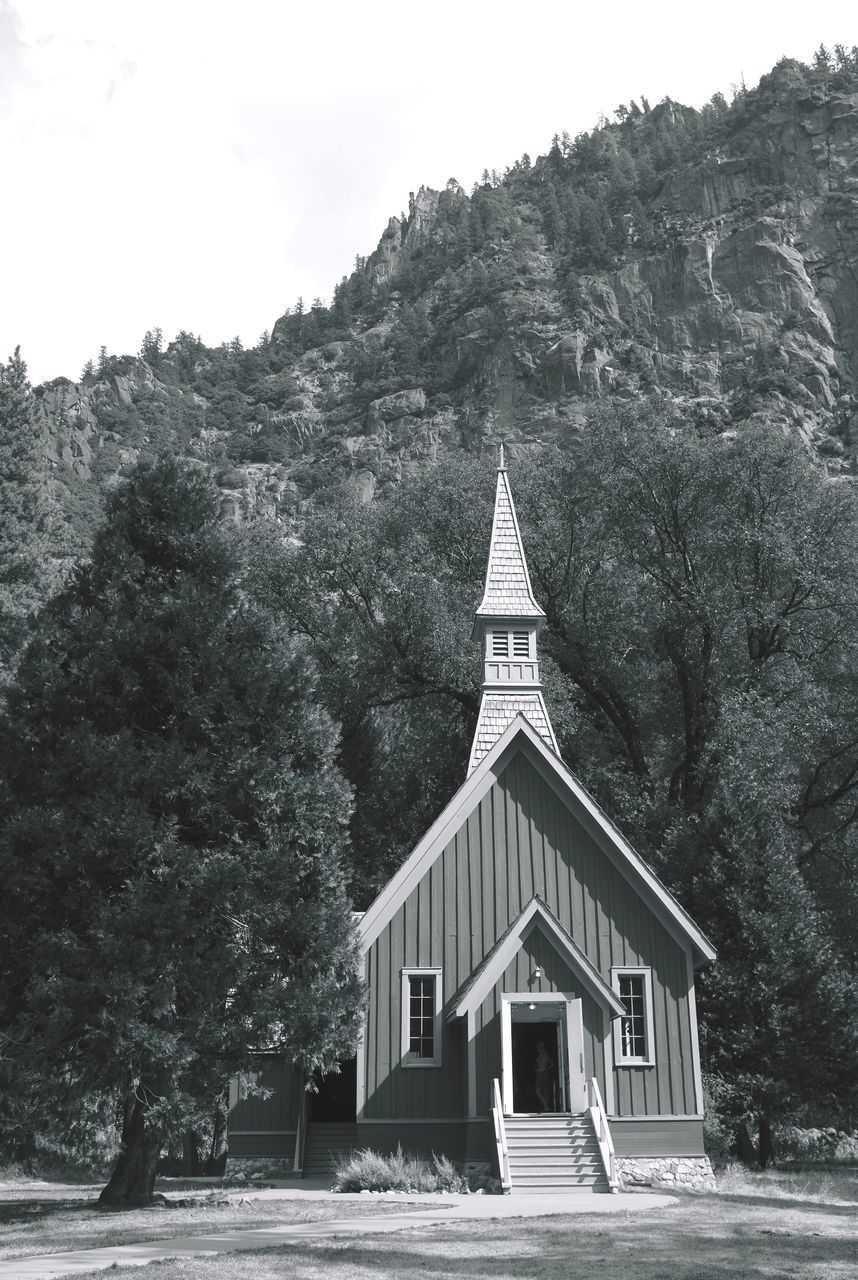 CHURCH BY BUILDING AGAINST MOUNTAIN