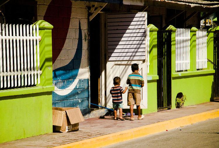 Children standing against built structure