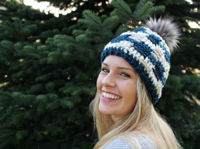 Close-up portrait of smiling woman wearing knit hat