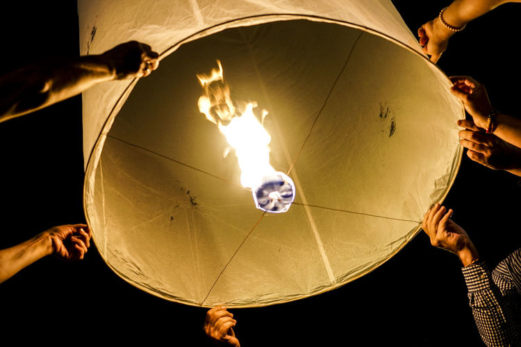Low angle view of people lighting lantern at night